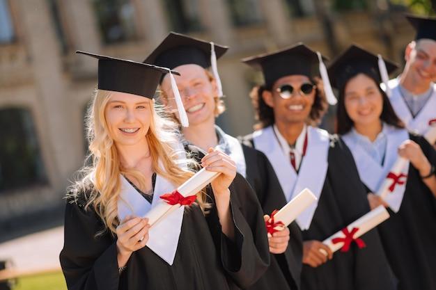 Uśmiechnięta blond dziewczyna stojąca przed swoimi wesołymi kolegami z grupy, kończącymi studia