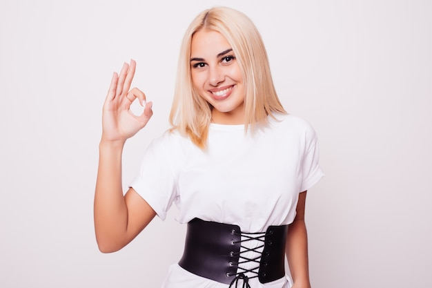 Uśmiechnięta blond kobieta pokazuje ok znak na białym tle