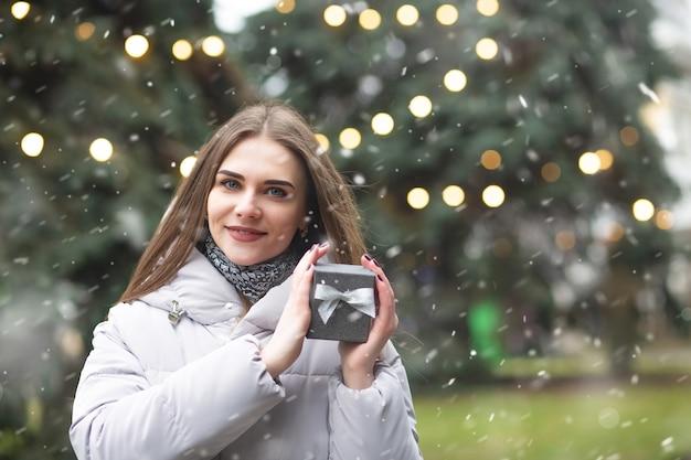 Uśmiechnięta blond kobieta trzyma pudełko podczas opadów śniegu. pusta przestrzeń