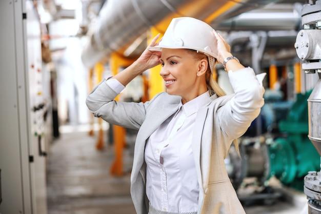 Uśmiechnięta blond kobieta w wizytowym stroju zakładając kask ochronny na głowę i przygotowując się do spaceru po elektrowni.