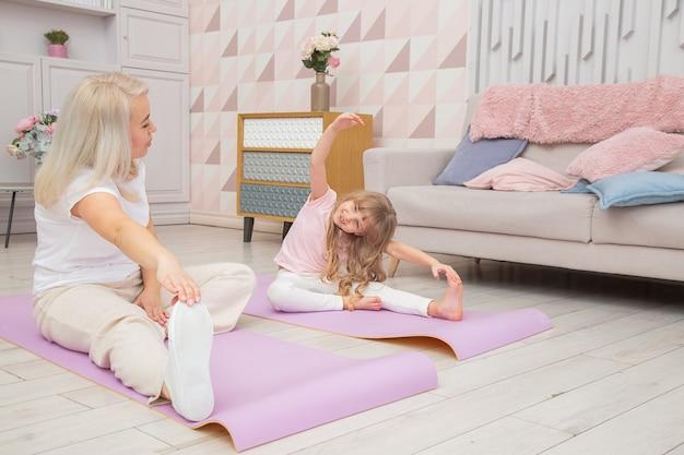 Uśmiechnięta blond matka na macie do jogi z uroczą zabawną córeczką w wieku przedszkolnym wykonuje różne ćwiczenia