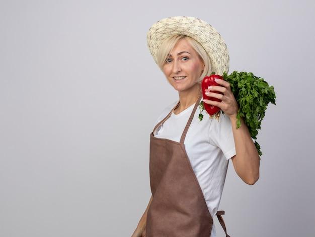 Uśmiechnięta blond ogrodniczka w średnim wieku w mundurze nosząca kapelusz stojący w widoku profilu trzymająca pęczek kolendry i pieprzu patrząca na przód na białym tle na białej ścianie z kopią przestrzeni