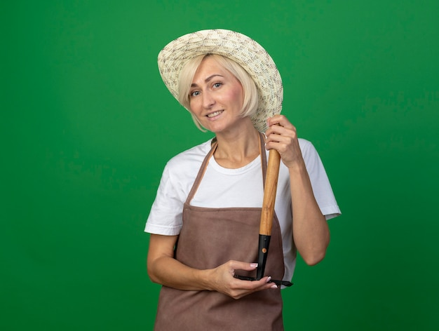 Uśmiechnięta blond ogrodniczka w średnim wieku w mundurze w kapeluszu trzymająca prowizję do góry nogami odizolowana na zielonej ścianie z miejscem na kopię