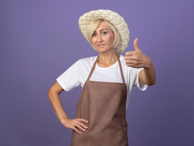 Uśmiechnięta blond ogrodniczka w średnim wieku w mundurze, w kapeluszu, trzymająca rękę w talii, pokazująca kciuk odizolowany na fioletowej ścianie