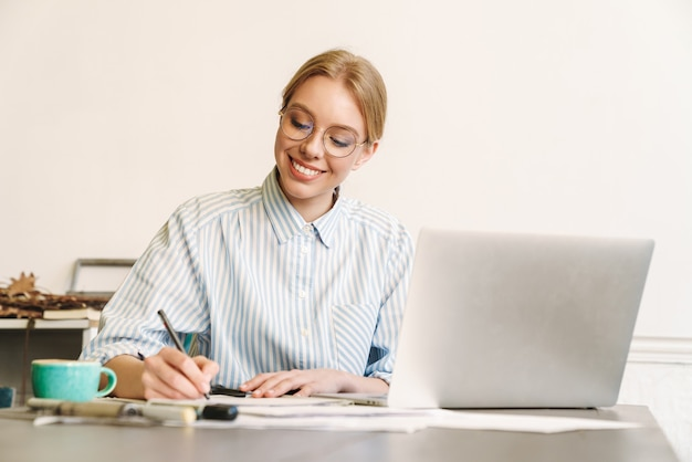 Uśmiechnięta blondynka architekt w okularach pracująca z laptopem podczas projektowania szkicu w miejscu pracy