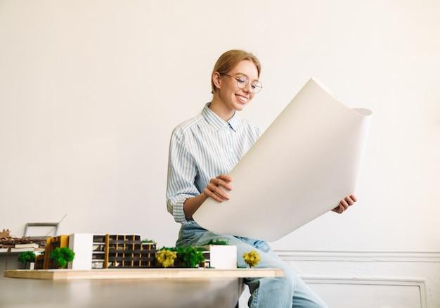 Uśmiechnięta blondynka architekt w okularach pracująca z rysunkami podczas projektowania szkicu w miejscu pracy