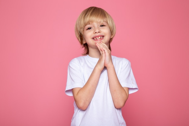 Uśmiechnięta blondynka dziecko słodkie słodkie urocze w białej koszulce na różowym biurku