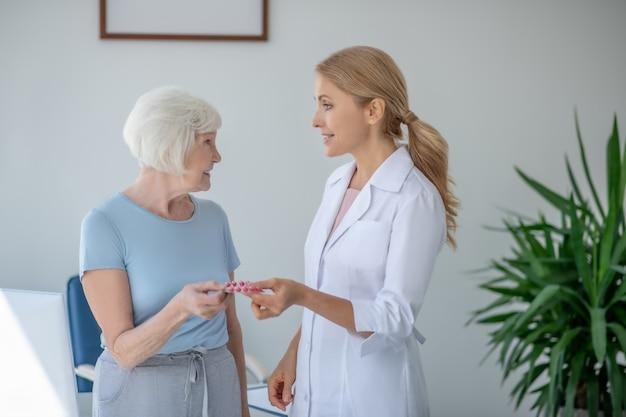 Uśmiechnięta blondynka lekarz dając blister z pils kobiecie