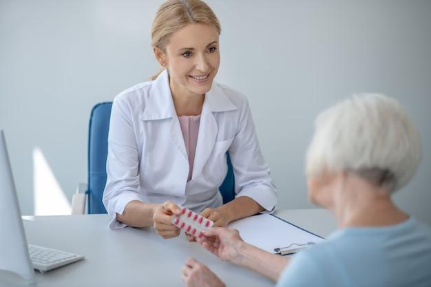 Uśmiechnięta blondynka lekarz daje blister z pils pacjentowi