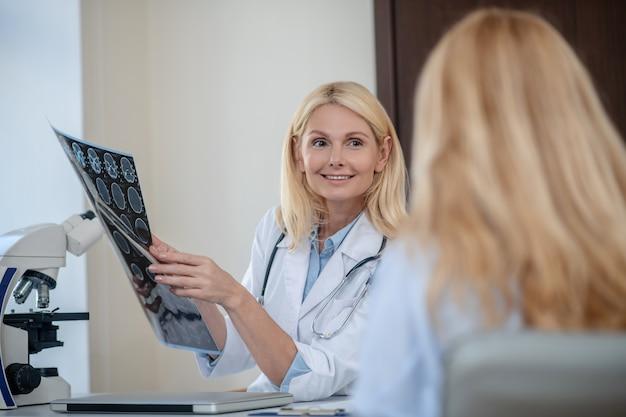 Uśmiechnięta blondynka lekarz pokazujący skan mrt i pacjent siedzący tyłem do aparatu