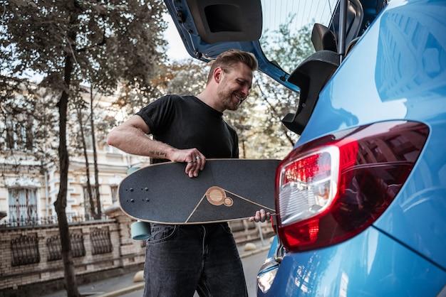 Uśmiechnięta blondynka mężczyzna łyżwiarz oddanie longboard do bagażnika samochodu śmiejąc się na tle miasta. sporty ekstremalne. miejskie hobby. koncepcja wypoczynku. czas wolny, koncepcja na zewnątrz.