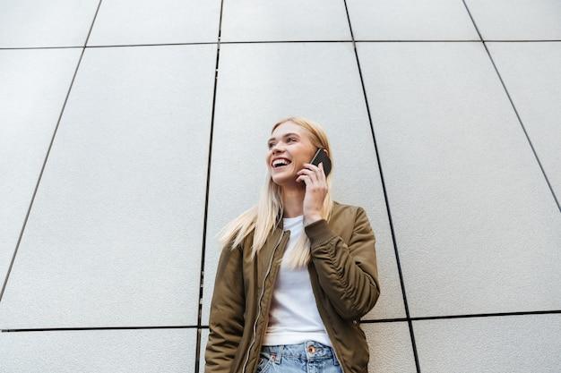 Uśmiechnięta blondynka opowiada na telefonie podczas gdy stojący blisko ściany