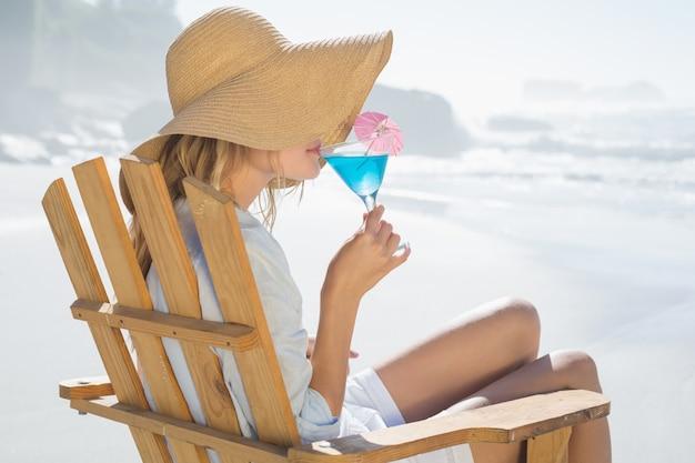 Uśmiechnięta blondynka relaksuje w pokładu krześle dennym popijaniem koktajlem