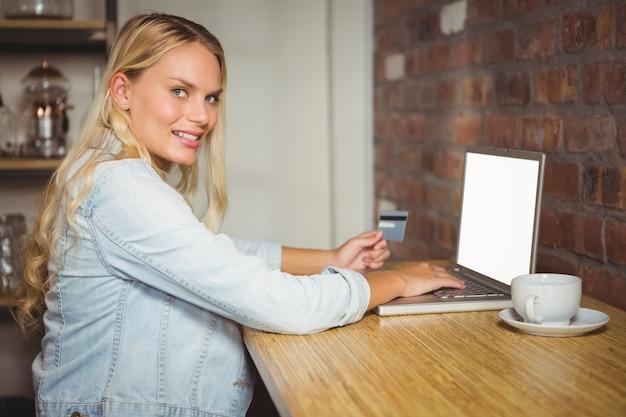 Uśmiechnięta blondynka robi zakupy online