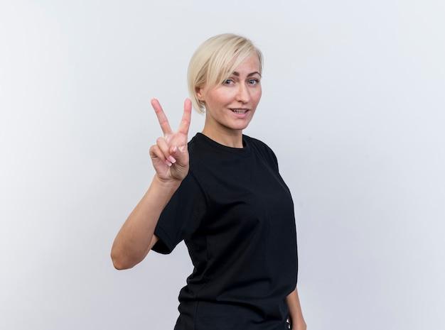 Uśmiechnięta blondynka słowiańska blondynka w średnim wieku robi znak pokoju patrząc na kamery na białym tle na białym tle z miejsca na kopię