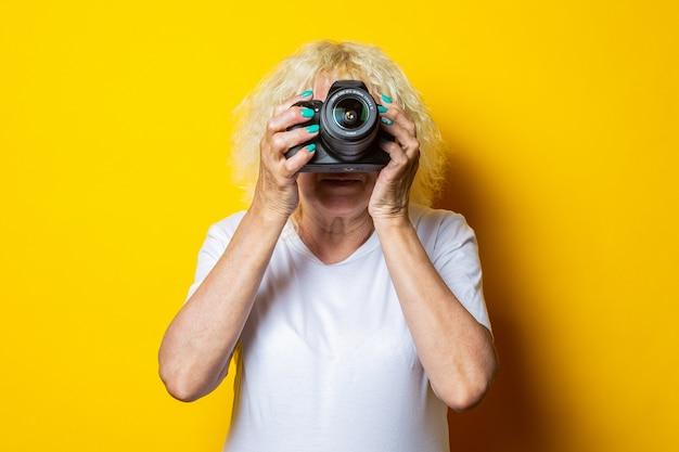 Uśmiechnięta blondynka stara kobieta w białej koszulce trzyma aparat i robi zdjęcia