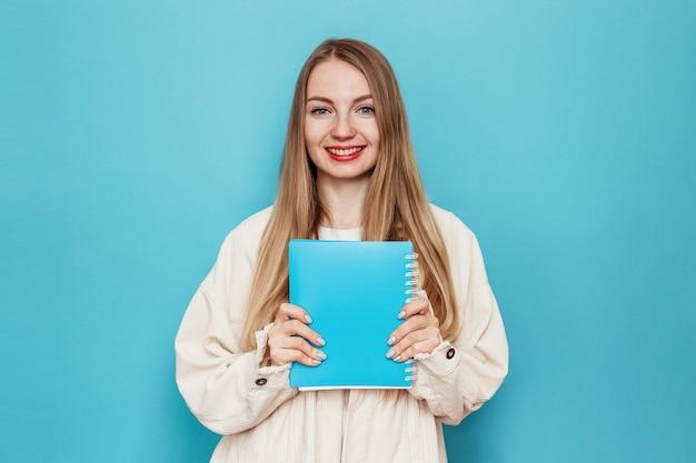 Uśmiechnięta blondynka studentka trzyma książkę, uśmiechnięty notebook, patrząc w kamerę na białym tle na niebieskiej ścianie