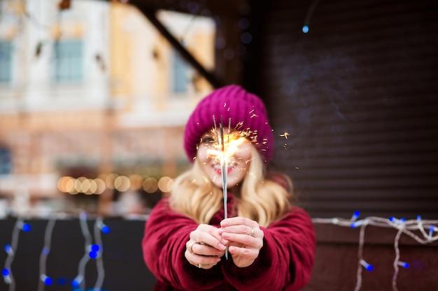 Uśmiechnięta blondynka trzyma świecące światła bengalskie na jarmarku bożonarodzeniowym w kijowie. efekt rozmycia