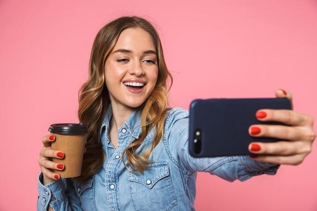Uśmiechnięta blondynka ubrana w dżinsową koszulę, pijąca kawę i robiąca selfie na smartfonie na różowej ścianie