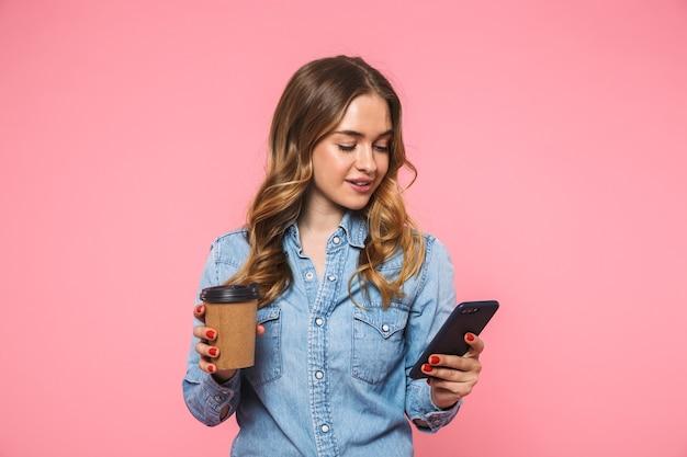 Uśmiechnięta blondynka ubrana w dżinsową koszulę trzymająca filiżankę kawy i używająca smartfona na różowej ścianie