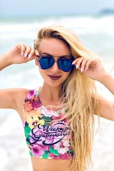 Uśmiechnięta blondynka w ciemnych okularach przeciwsłonecznych pozowanie na tle morza. plenerowy portret jasnowłosej kobiety w podkoszulku z kwiatowym nadrukiem, relaksujący w nadmorskim kurorcie latem.