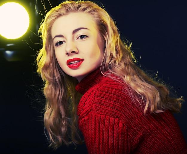 Uśmiechnięta blondynka w czerwonym swetrze