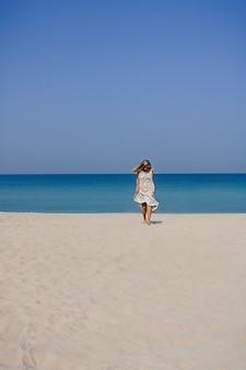 Uśmiechnięta blondynka w lnianej sukience maxi z fruwającymi włosami, skacząca i tańcząca na piaszczystej plaży