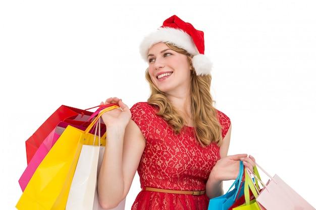 Uśmiechnięta blondynka w santa kapeluszu mienia torba na zakupy