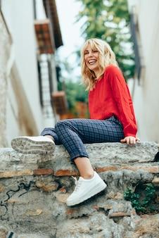 Uśmiechnięta blondynki dziewczyna z czerwoną koszula cieszy się życie outdoors.