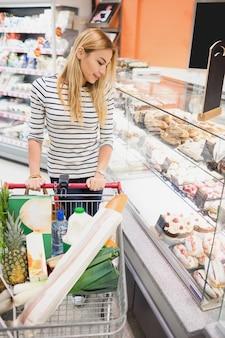 Uśmiechnięta blondynki kobieta patrzeje deser półkę