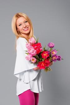 Uśmiechnięta blondynki kobieta z kwiatem wiosny