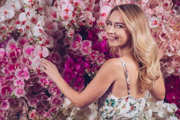 Uśmiechnięta blondynki młoda kobieta dotyka orchidei kwitnie patrzejący kamerę