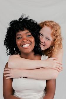 Uśmiechnięta blondynki młoda kobieta obejmuje jej afrykańskiego przyjaciela przeciw popielatemu tłu
