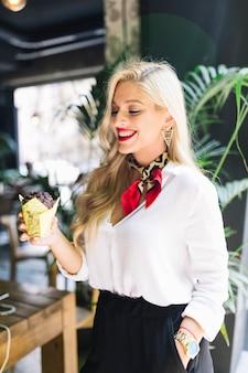Uśmiechnięta blondynki młoda kobieta z ręką na kieszeniowym mienia słodka bułeczka w papierowym właścicielu