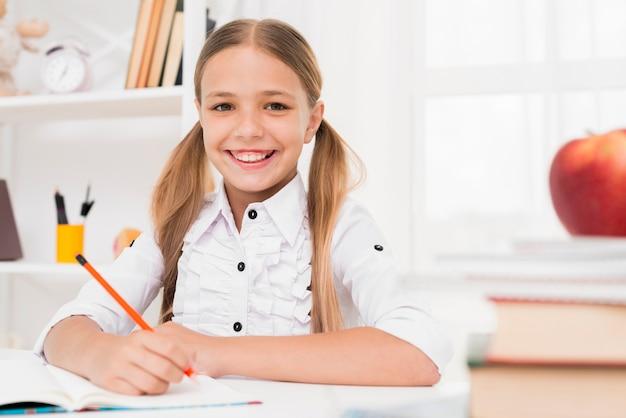 Uśmiechnięta blondynki szkoły podstawowej dziewczyna robi pracie domowej