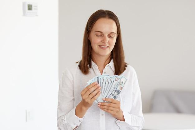 Uśmiechnięta bogata atrakcyjna kobieta o ciemnych włosach, ubrana w białą koszulę w stylu casual, licząca pieniądze podczas pozowania w domu w jasnym pokoju, mająca zadowolony wyraz twarzy.