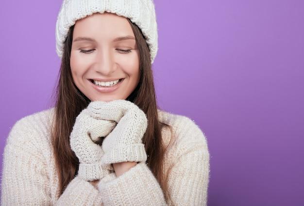 Uśmiechnięta brązowowłosa kobieta w dzianinowym kapeluszu i rękawicach z jednym palcem położyła ręce na brodzie.