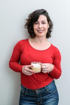 Uśmiechnięta brazylijka stoi przed kamerą i trzyma filiżankę cappuccino (zdjęcie w pionie).