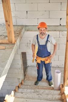 Uśmiechnięta brodata dojrzała w kasku stojąca na schodach