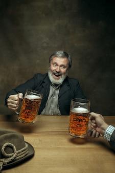 Uśmiechnięta brodata samiec pije piwo w pubie