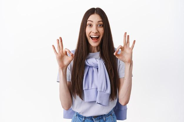 Uśmiechnięta brunetka bezgranicznie zakochana w rabatach, pokazująca dobry gest ok, gest tak, kiwnięcie głową z aprobatą, stojąca nad białą ścianą