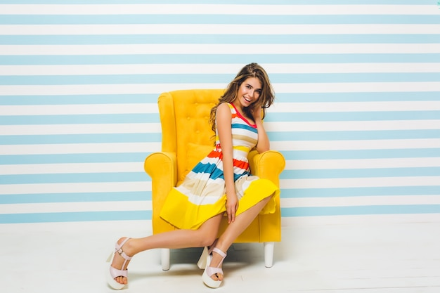 Uśmiechnięta brunetka dziewczyna w jasnej letniej sukience pozowanie w pomieszczeniu, siedząc w dużym żółtym fotelu. portret pięknej młodej kobiety z jasnobrązowymi włosami odpoczywającej w swoim pokoju na ścianie w paski.