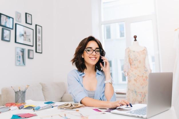 Uśmiechnięta brunetka dziewczyna w niebieskiej koszuli siedzi przy stole w studio. mówi przez telefon i pisze na komputerze. ona uśmiecha się do kamery.