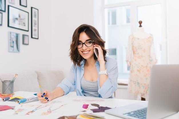 Uśmiechnięta brunetka dziewczyna w niebieskiej koszuli siedzi przy stole w studio. mówi przez telefon i trzyma w ręku ołówek. ona uśmiecha się do kamery.