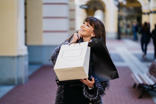 Uśmiechnięta brunetka gorgeus z długimi prostymi włosami w futrze i białą spódnicą stojącą na tle klasycznego budynku z torbami na zakupy