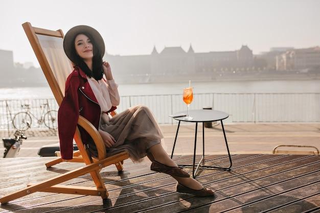 Uśmiechnięta brunetka kobieta siedzi na fotelu, ciesząc się wakacjami w europie