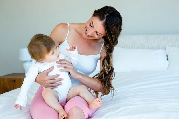 Uśmiechnięta brunetka kobieta siedzi w dół trzyma słodkie dziecko na łóżku