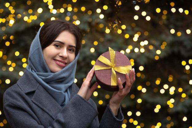Uśmiechnięta brunetka kobieta trzyma pudełko w pobliżu choinki. miejsce na tekst