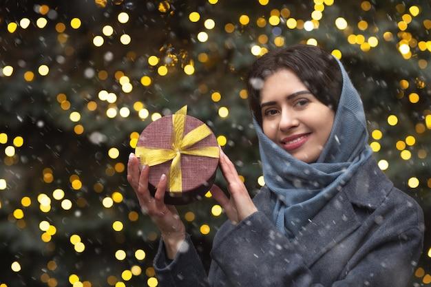 Uśmiechnięta brunetka kobieta trzyma pudełko w pobliżu choinki podczas opadów śniegu. miejsce na tekst