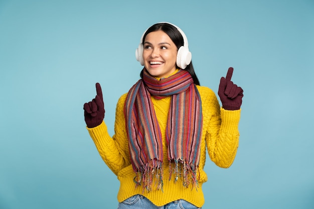 Uśmiechnięta brunetka kobieta ubrana w żółty sweter z dzianiny, szalik i nauszniki, gestykuluje i uśmiecha się, pozując na białym tle na niebieskim tle studio. koncepcja ciepłej zimy i zimnej pory roku